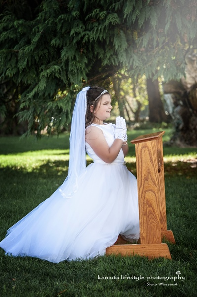 First Holy Communion Girl on the kneeler in the park